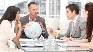 Gerente sostiene un globo terrestre en una reunión — Vídeo de Stock