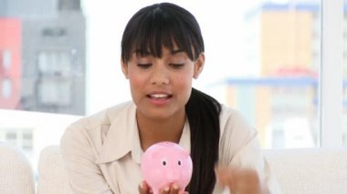 Ethnic businesswoman holding a piggy-bank — Stock Video
