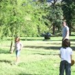 Family playing baseball in a park - Stock Photo