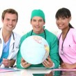 International medical team holding a terrestrial globe — Stock Video