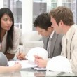 Stock Video: Group of architects studying blueprints