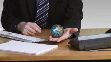 Biznesmen z obrotowym globu ziemskiego w jego dłoni — Wideo stockowe