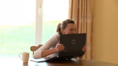 Blissful woman using a laptop and drinking coffee — Stock Video