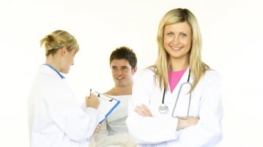 Beautiful female doctors smiling at the camera and a male patient in bed in the background in High Definition