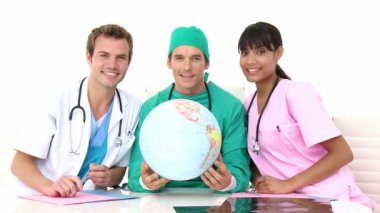 équipe médicale internationale tenant un globe terrestre — Vidéo