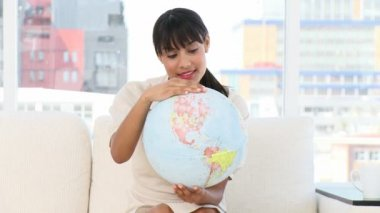 Young businesswoman looking at a terrestrial globe — 图库视频影像