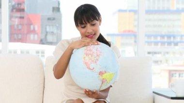 Jonge zakenvrouw kijken naar een terrestrische globe — Stockvideo