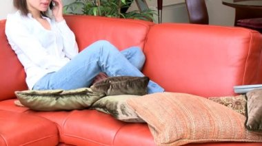 Jolly woman talking on phone sitting on sofa — Stock Video