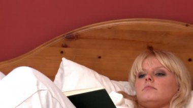 Delightful woman lying on bed reading a book — Stock Video