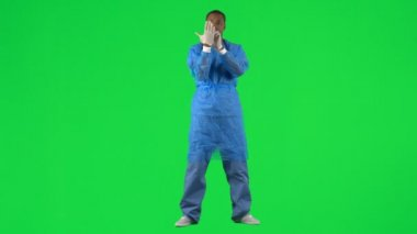 Footage of an ethnic surgeon putting on gloves against green screen in high definition
