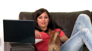 Laughing woman and her dog using a laptop — Vídeo de stock