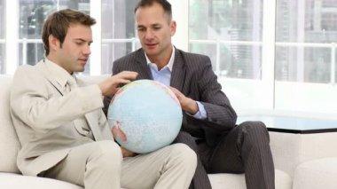 серьезные бизнесмены, глядя на земной шар — Стоковое видео