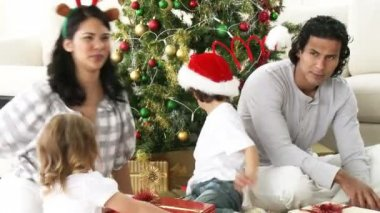 Parents and children opening Christmas presents at home — Stock Video