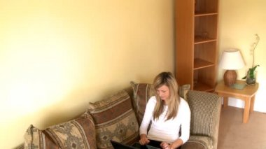 Enthusiastic woman looking at her laptop sitting on sofa — Stock Video