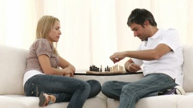 Couple playing chess on sofa in living-room. Footage in high definition