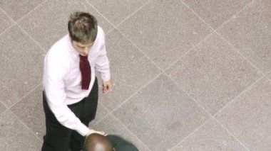 High angle of businessman on phone and shaking hands with a colleague at work