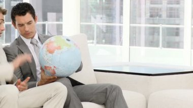 Businessmen looking at a terrestrial globe — Стоковое видео