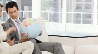 Empresarios mirando un globo terrestre — Vídeo de Stock