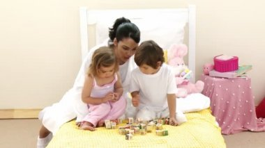 Mother, daughter and son playing with toy cubes on the bed — Stock Video