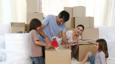 Footage in high definition of young parents and children moving house packing boxes