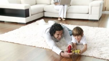 Father and son playing video games on floor and mother using a laptop — Stock Video