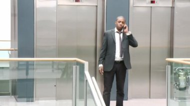 Afro-American businessman on phone in a building — Stock Video
