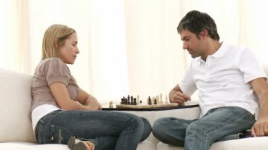 Woman and man playing chess on sofa in living-room — Stock Video