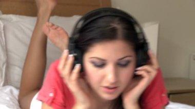 Elegant woman lying down on bed listening music — Stock Video