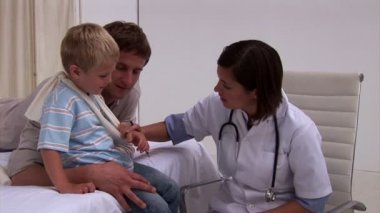 Assertive doctor examining a little boy's arm — Stock Video