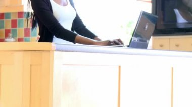 Smiling woman in the kitchen using a laptop — Stock Video