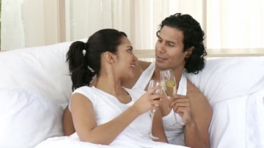 Happy couple drinking champagne in bedroom celebrating an anniversary. Footage in high definition