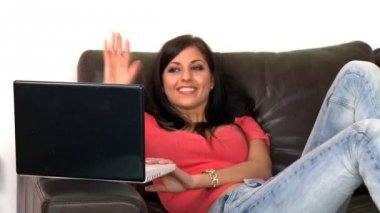 Smiling woman using a laptop sitting on sofa — Stock Video