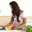 Happy woman using laptop while preparing dinner — Stock Video #15448293