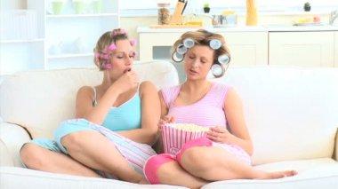 Mulheres jovens com rolos de cabelo comendo pipoca no sofá — Vídeo Stock