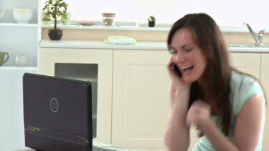 Excited woman phoning and using her laptop — Stock Video