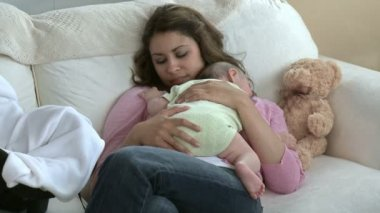 Attentive young mother with her beautiful baby on a sofa — Stock Video
