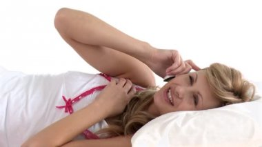 Delighted woman talking on phone lying on a bed — Vidéo