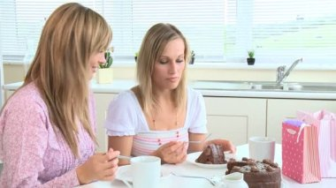 Happy young women eating chocolate cake — Vídeo de stock