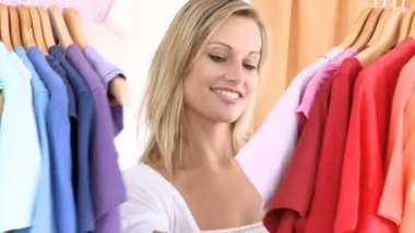 Delighted woman looking for a shirt — Vidéo