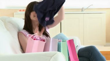 Cheerful young caucasian woman opening shopping bags sitting on a sofa — Vídeo Stock
