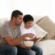 Stock Video: Father and son watching televison on sofa