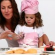Stock Video: Mother helping her daughter to bake
