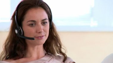 Smiling woman having a discussion through a headset — Stock Video
