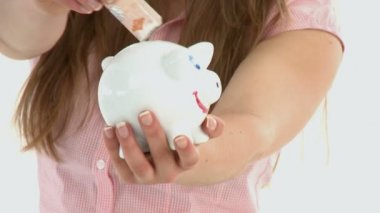 Close-up of woman putting money in a piggybank — Stock Video #15453041