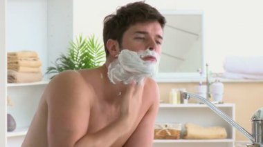 Cute man applying cream on his face before shaving in the bathroom at home