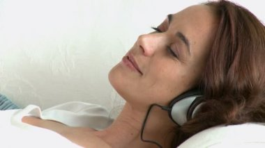 Relaxing hispanic woman lying on the sofa and listening to music with headphones — Stock Video