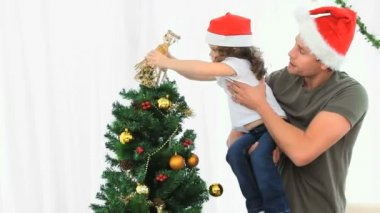 Father helping his daughter to decorate the Christmas tree against a white background