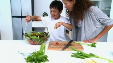 Boy cooking a salad with his mother — Stock Video