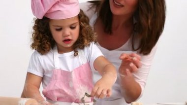 Attentive mother helping her daughter to bake — Stock Video