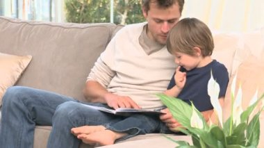 Man reading a book with his son — Vídeo de stock